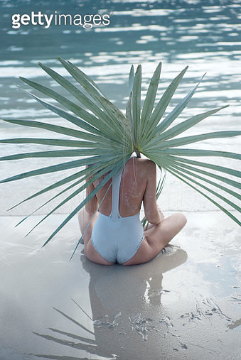 Woman with palm leaf sitting near water on the beach - gettyimageskorea