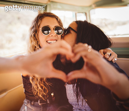 Woman kissing her girl friend on cheek with hand heart - gettyimageskorea