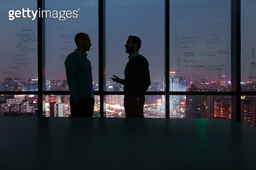 Men talking at night in office with city view - gettyimageskorea