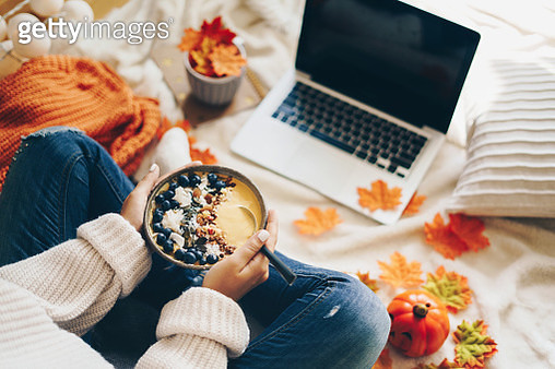 Woman having healthy breakfast and using laptop - Autumn concept - gettyimageskorea