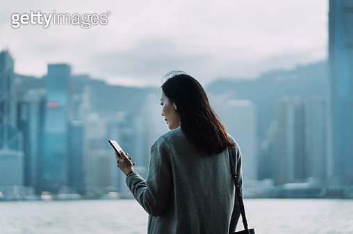 Young Asian businesswoman using smartphone by the promenade of Victoria harbour, against Hong Kong city scene of central business district - gettyimageskorea