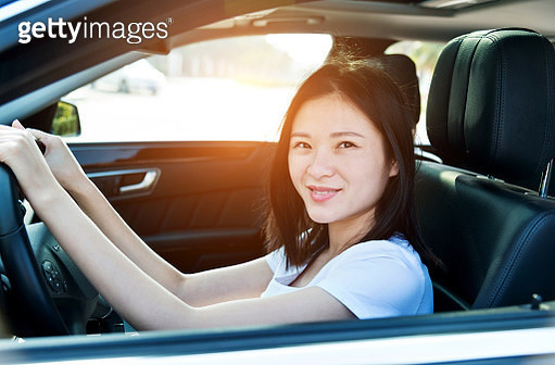 Beautiful woman smiling and driving a car - gettyimageskorea