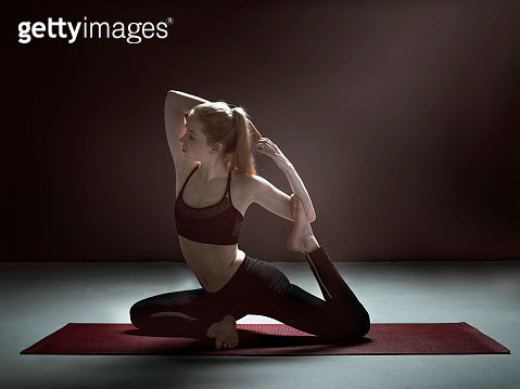 Flexible woman doing yoga in mermaid pose - gettyimageskorea