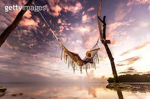 Low angle view of happy woman relaxing in hammock above the sea at sunset. Copy space. - gettyimageskorea