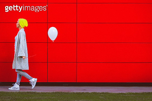 Young woman holding white balloon while walking beside the red wall - gettyimageskorea