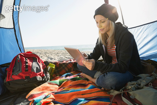 Woman using digital tablet in tent on beach - gettyimageskorea