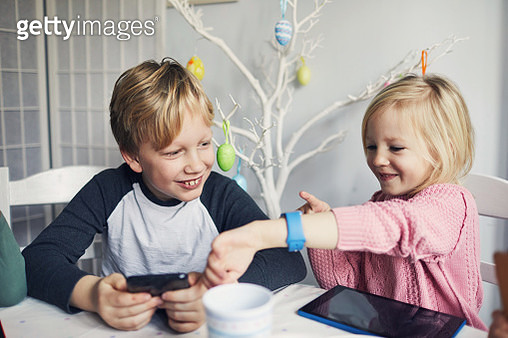 Children using looking at a smart watch together - gettyimageskorea