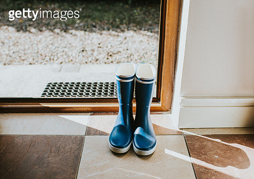 Blue Welly boots sitting by an open back door. - gettyimageskorea