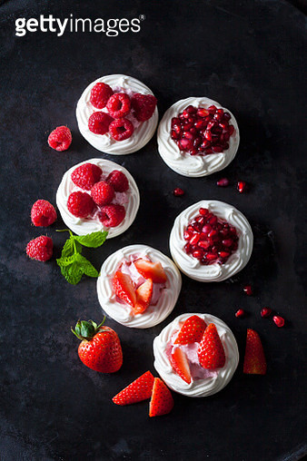 Meringue pastries garnished with whipped cream, berries and pomegranate seed - gettyimageskorea