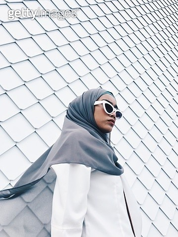 Woman Wearing Sunglasses And Hijab While Standing Against Wall - gettyimageskorea