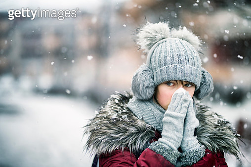 Teenage girl blowing nose on winter day - gettyimageskorea