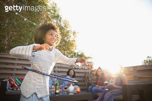 Girl spinning in plastic hoop on sunny deck - gettyimageskorea