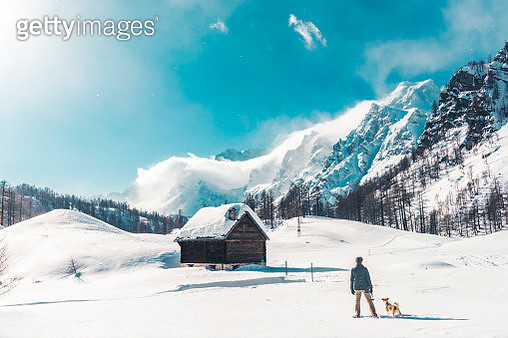 Man with dog at the leash in winter alps. - gettyimageskorea