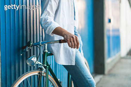 Man with bicycle leaning on blue garage door - gettyimageskorea