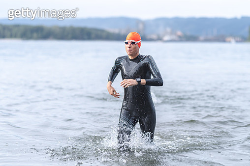 A middle-aged female triathlete runs out of the water after completing the swim stage. She is wearing a wetsuit, goggles, and swim cap. - gettyimageskorea