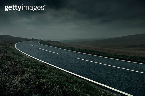 Curved road through stormy landscape - gettyimageskorea