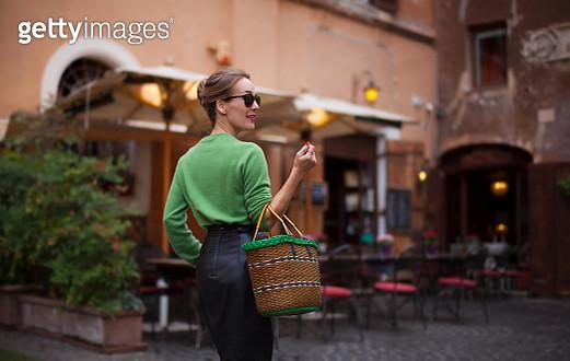 Elegant woman walking on Roman city street, holding basket - gettyimageskorea