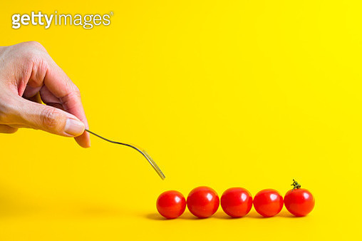 Cropped Hand Holding Fork With Tomatoes On Yellow Background - gettyimageskorea
