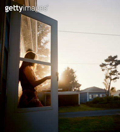 Young woman walking through door, side view - gettyimageskorea