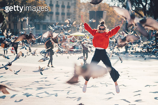 Young girl at Placa de Catalunya jumping happily among the pigeons - gettyimageskorea