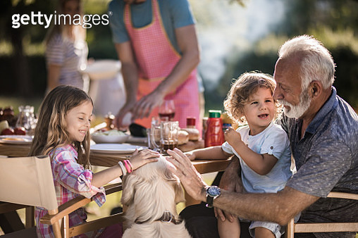 Senior grandfather enjoying with his grandkids while waiting for lunch in the backyard. - gettyimageskorea