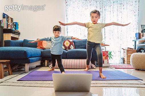 Little sibling enjoy online yoga class with laptop computer at home. - gettyimageskorea