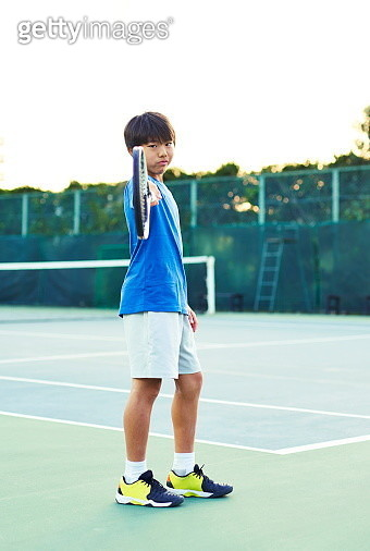 Portrait of teenage boy holding a tennis racket make a powerful pose - gettyimageskorea