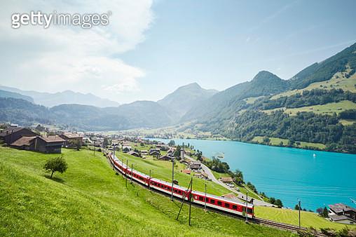 Lush Swiss landscape with commuter train and lake, Lungern, Obwalden, Switzerland - gettyimageskorea