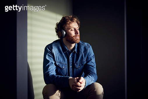 Relaxed casual businessman sitting down listening to music with headphones - gettyimageskorea