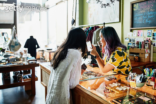 Shopkeeper showing client information on smart phone while checking out at counter in boutique - gettyimageskorea