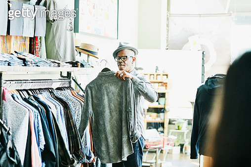 Senior man looking at shirt while shopping in clothing boutique - gettyimageskorea