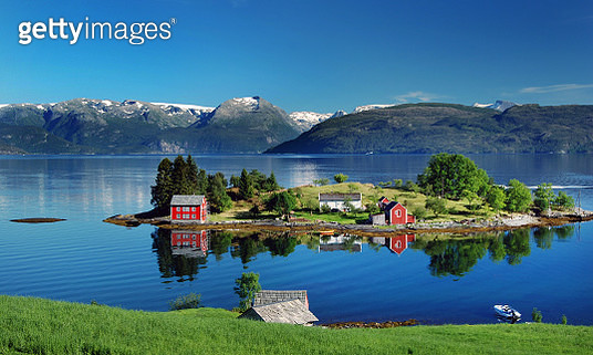 Hardangerfjord in south western Norway in the summer. A red, Norwegian house situated on a small island in the fjord. In the distance the Folgefonna glacier. Photo was taken near the village of Omastranda. - gettyimageskorea