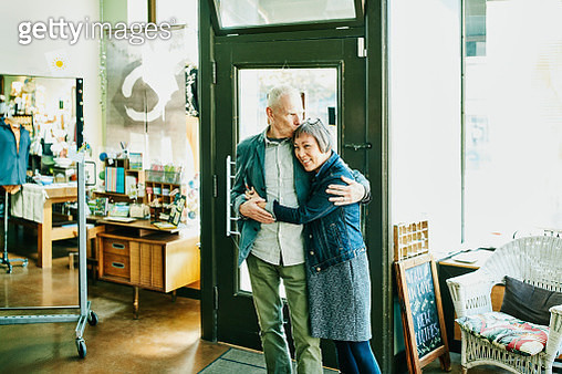 Portrait of embracing shop owners in boutique - gettyimageskorea
