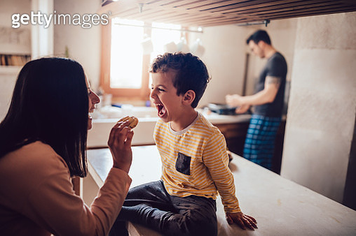 Cheerful mother giving little son cookie in the morning - gettyimageskorea