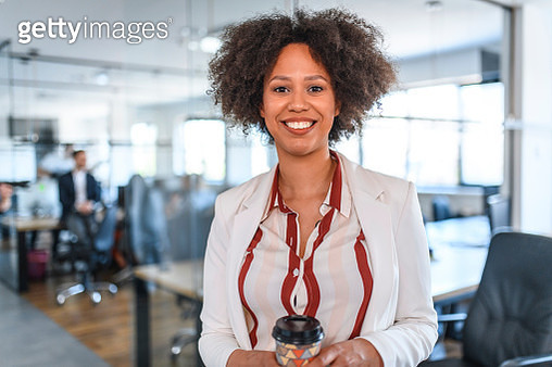 Smiling and relaxed mixed race business woman standing with coffee in an open plan office with colleagues in the background. - gettyimageskorea