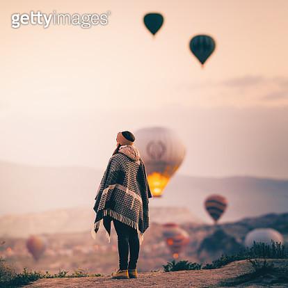 Tourist woman admiring hot air balloons rising in Cappadocia - gettyimageskorea
