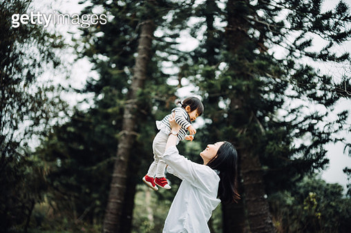 Joyful mother enjoying happy family time with cute toddler girl and lifting her in the air in nature park - gettyimageskorea