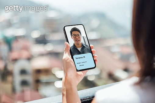 Young Woman Using Dating App On Smart Phone - gettyimageskorea
