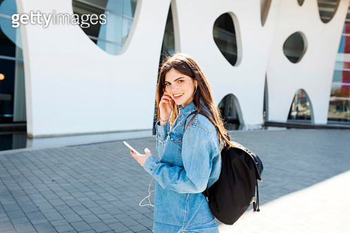 Spain, Barcelona, portrait of smiling young woman with backpack listening music with cell phone and earphones - gettyimageskorea