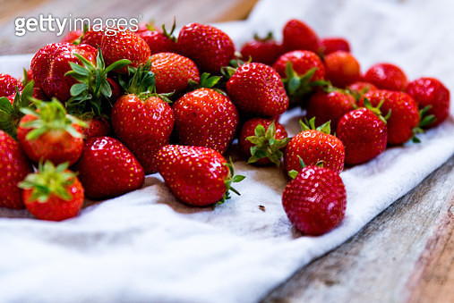 Close-Up Of Strawberries On Cloth At Table - gettyimageskorea