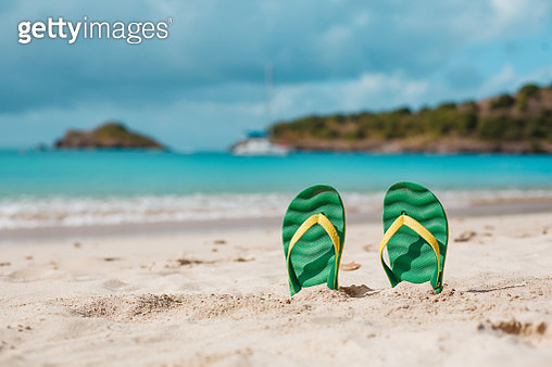 Green flipflops in the white sandy beach near sea waves, nobody. Summer vacation concept with blue water. Relax, vacation on tropical island. Copyspace - gettyimageskorea