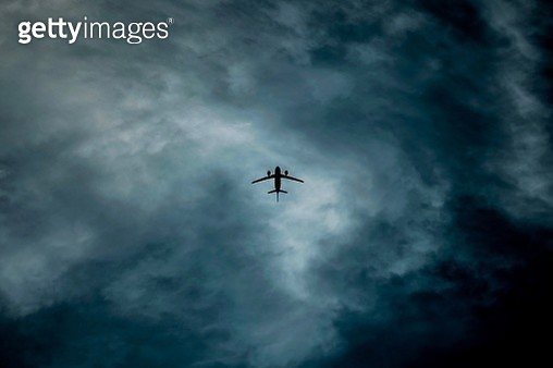 Low Angle View Of Airplane Flying Against Storm Cloud - gettyimageskorea