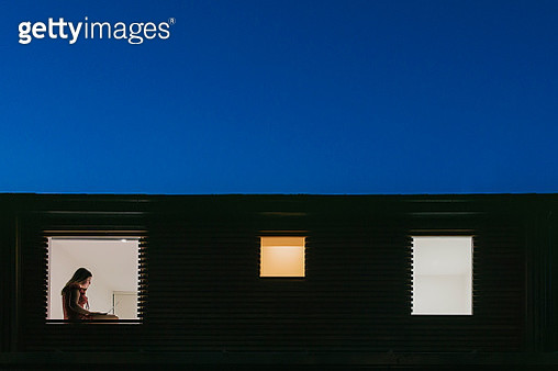 Night time view of home exterior - figure on laptop in the window - gettyimageskorea