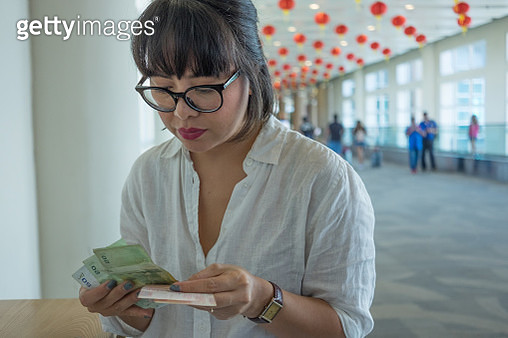 Bali, Indonesia, Asian woman at airport departures, counting money - gettyimageskorea