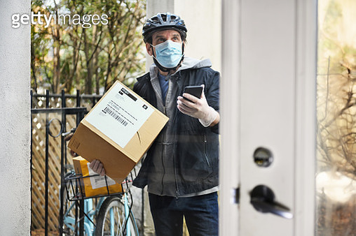 Mature man delivering parcel with contactless payment - gettyimageskorea