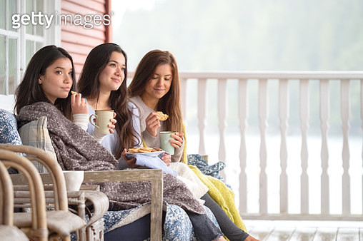 Weekend Getaway, Sisters Enjoying Coffee and Cookies on Cabin Deck - gettyimageskorea
