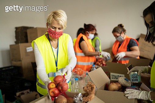 Woman with protective face mask helping collecting food in a homeless shelter - gettyimageskorea