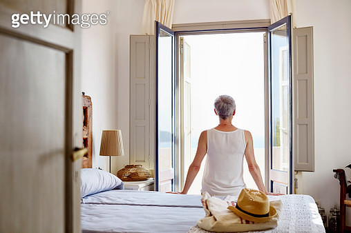 Rear view of senior woman sitting on bed at home - gettyimageskorea