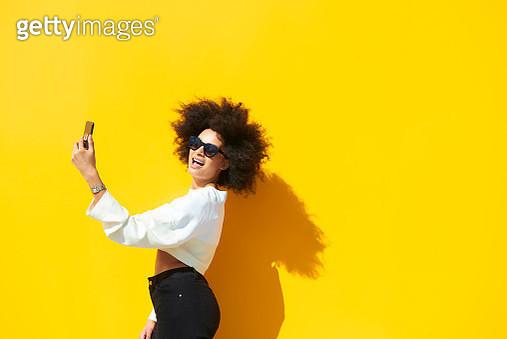 Woman taking selfie against yellow background - gettyimageskorea