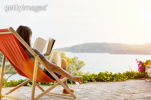 Woman reading book while relaxing on deck chair at back yard - gettyimageskorea